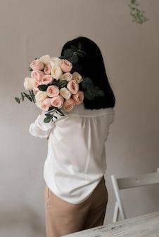 Mooi meisje met een boeket bloemen van roze rozen op een datum. bedrijfsvrouw met een boeket bloemen. uitzicht vanaf de achterkant.