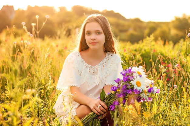 Mooi meisje met een boeket van wilde bloemen in een veld in de zomer