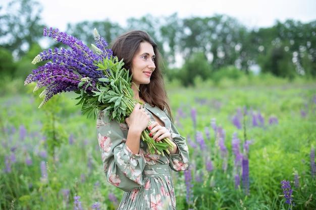 Mooi meisje met een boeket wilde bloemen vrouw met een boeket lupine staat in bloemenveld