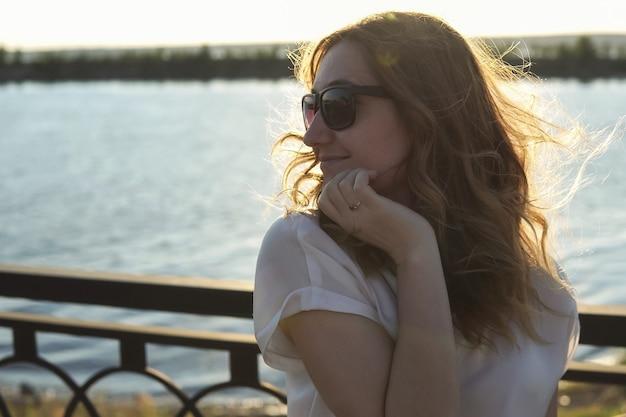 Mooi meisje met een bril aan de waterkant en glimlachend in de camera bij zonsondergang