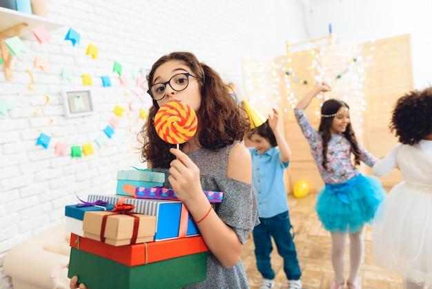 Mooi meisje met een bril en een heleboel geschenken in handen.