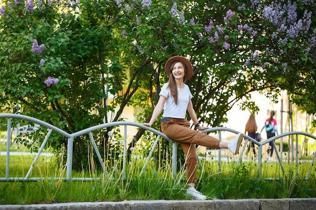 Mooi meisje met een bruine hoed die zich dichtbij een lila struik bevindt. stijlvolle jonge vrouw in een hoed in de buurt van een bloeiende boom. ze lacht en geniet van het leven op een warme zomerdag.