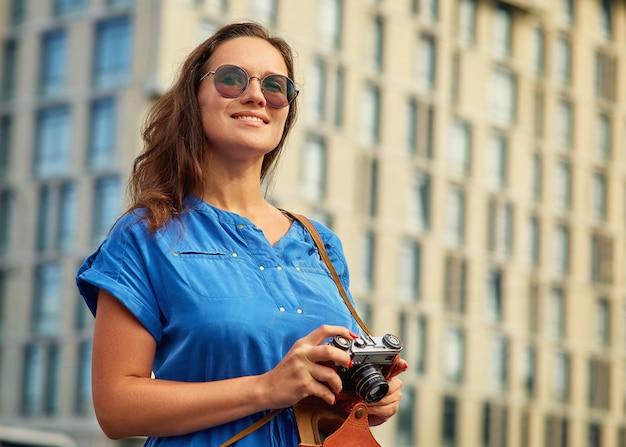 Mooi meisje met een camera in een blauwe jurk op de achtergrond van het gebouw