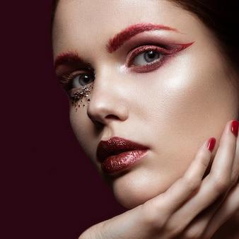 Mooi meisje met een felrode mode make-up en kristallen op het gezicht. Premium Foto