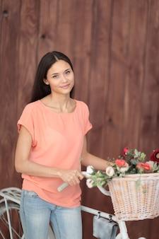 Mooi meisje met een fiets met een mooie mand vol bloemen