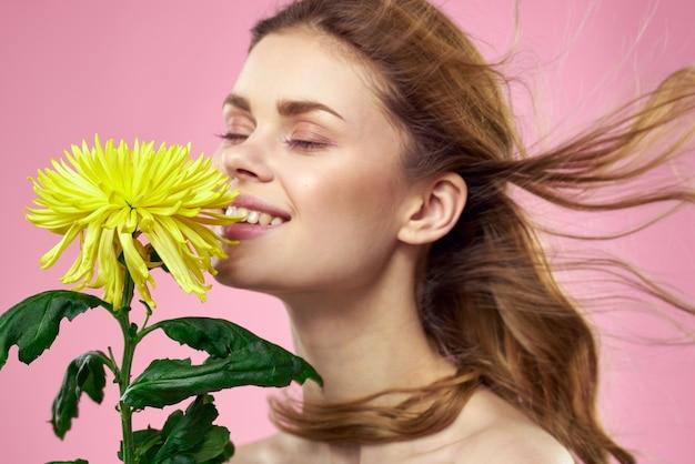 Mooi meisje met een gele bloem op een roze muur