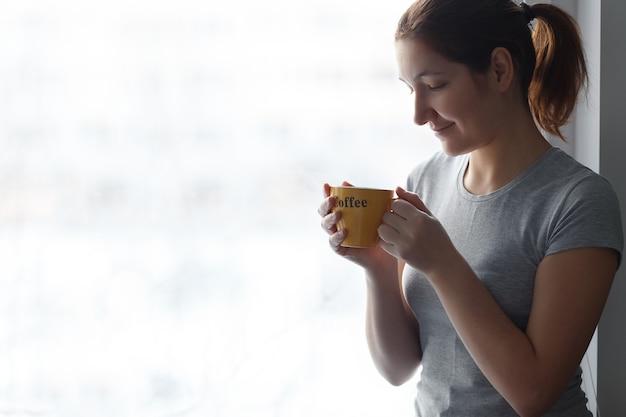 Mooi meisje met een gele kop met inscriptie koffie bij raam.