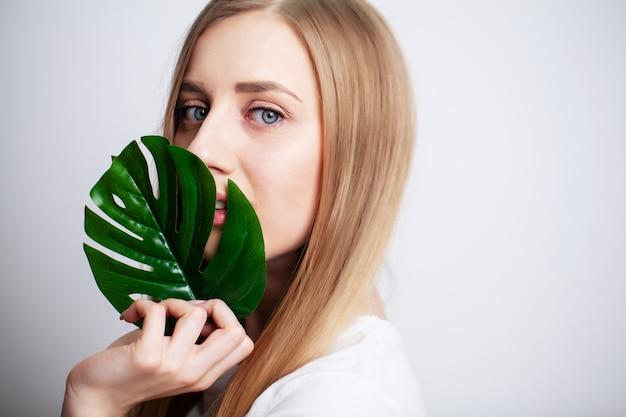 Mooi meisje met een gezonde huid en groene plant