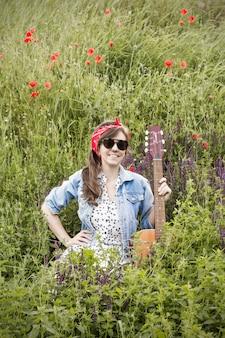 Mooi meisje met een gitaar in papavers.