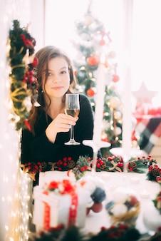 Mooi meisje met een glas champagne, kerstmis en nieuwjaarsachtergrond
