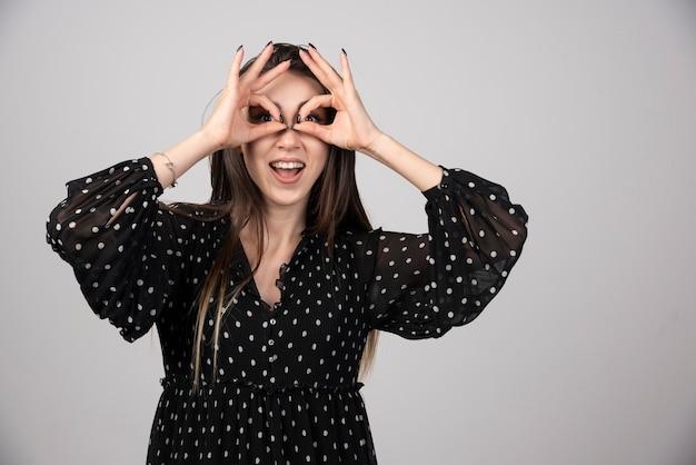 Mooi meisje met een glimlach die vingers houdt in de buurt van ogen als een bril.
