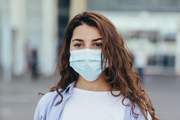 Mooi meisje met een grote koffer op de luchthaven met een beschermend masker op haar gezicht