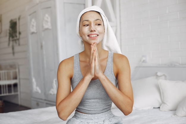 Mooi meisje met een handdoek die een schoonheidsproduct gebruikt