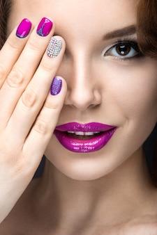 Mooi meisje met een heldere avond make-up en paarse manicure met strass steentjes. nagel ontwerp. mooi gezicht. foto genomen in de studio op een zwarte achtergrond.