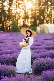 Mooi meisje met een hond in een mand in lavendel. ze draagt een lange jurk en een grote hoed ...