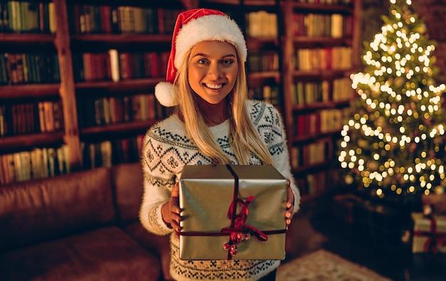 Mooi meisje met een kerstcadeau voor haar. gelukkige vrouw in kerstmanhoed die zich dichtbij nieuwjaarsboom bevindt en op viering wacht.