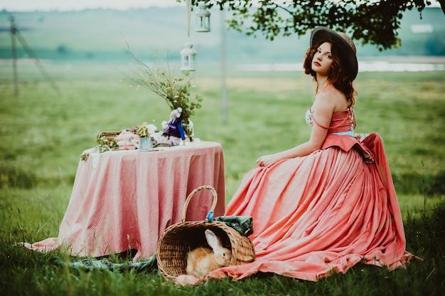 Mooi meisje met een konijn buiten in de zomerdag