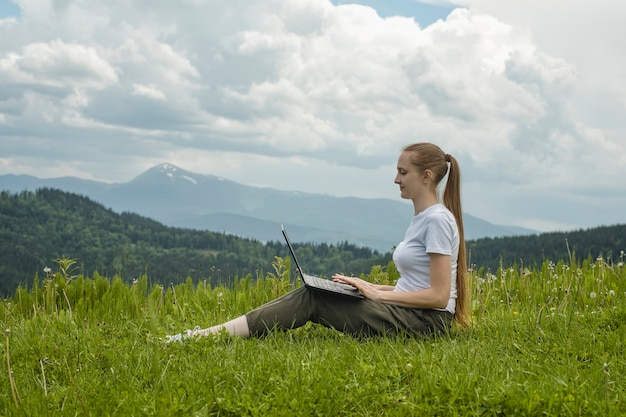 Mooi meisje met een laptop zitting op groen gras