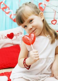 Mooi meisje met een lolly in de vorm van een hart