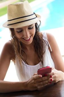 Mooi meisje met een mobiele telefoon bij het zwembad.