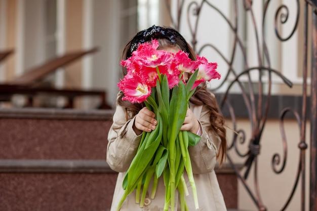Mooi meisje met een mooi feestelijk boeket van verse roze tulpen, die haar gezicht met hen. jong meisje dat tulpen geeft. een kind met bloemen in zijn handen.