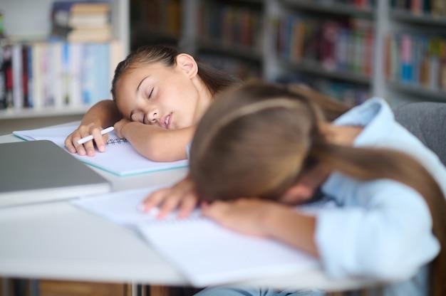 Mooi meisje met een pen en haar uitgeputte vriend die samen dommelt