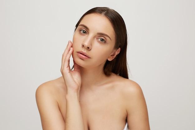 Mooi meisje met een perfecte gezonde frisse huid raakt haar wang
