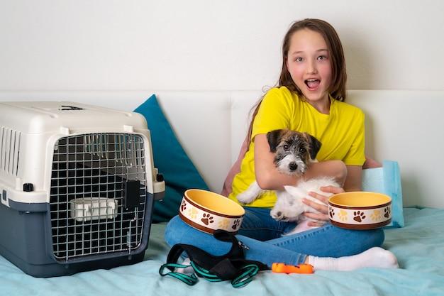 Mooi meisje met een puppy van jack russell terrier. artikelen voor hondenverzorging.