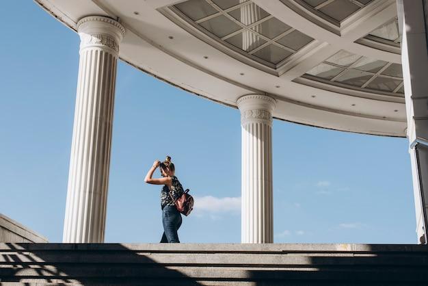 Mooi meisje met een rugzak in een stedelijke omgeving een vrouw loopt op een zonnige dag door de stad klassieke kolommen van de stadsarchitectuur
