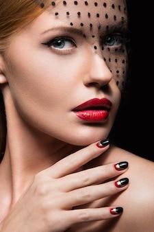 Mooi meisje met een sluier, avondmake-up, zwarte en rode nagels