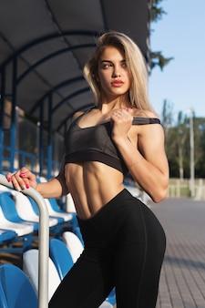 Mooi meisje met een sportief lichaam poseren in het stadion