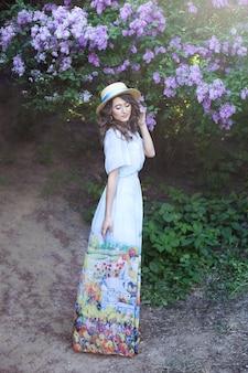 Mooi meisje met een strohoed in een lila tuin meisje met lila bloemen in de zomer tuinieren zomerbloemen lentebloesem