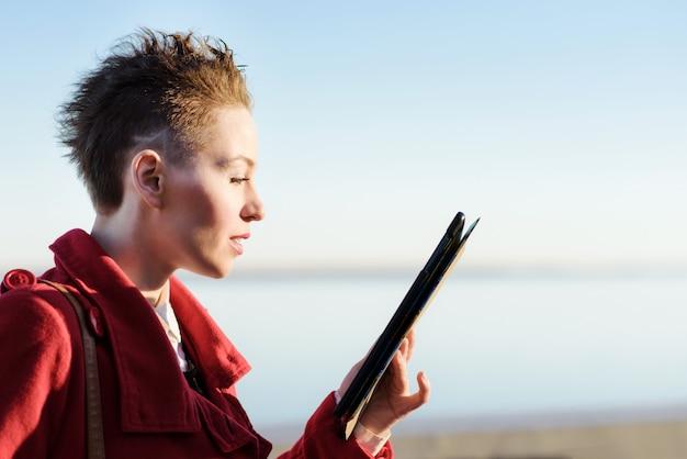 Mooi meisje met een tablet die zonnige dag stellen