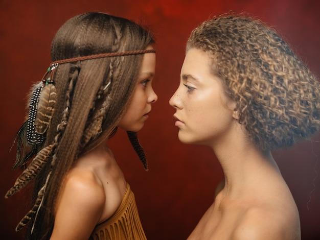 Mooi meisje met een veer in haar haar en vrouw aboriginals rode achtergrond familie indische stam