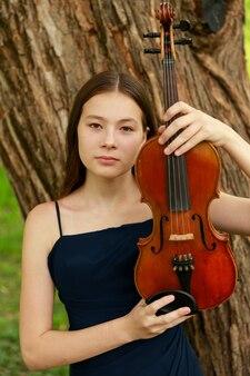Mooi meisje met een viool bij de boom in het park. hoge kwaliteit foto