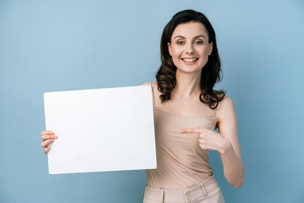 Mooi meisje met een wit vel papier wijst haar vinger erop.
