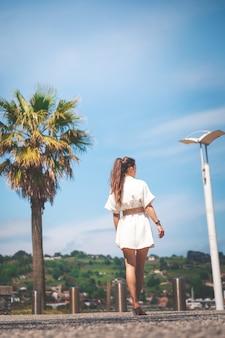 Mooi meisje met een witte jurk die door een kustdorp loopt