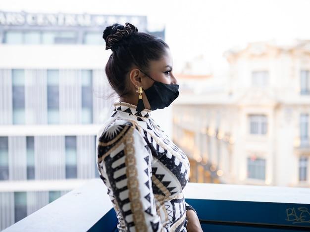 Mooi meisje met een zwart medisch masker in de stad