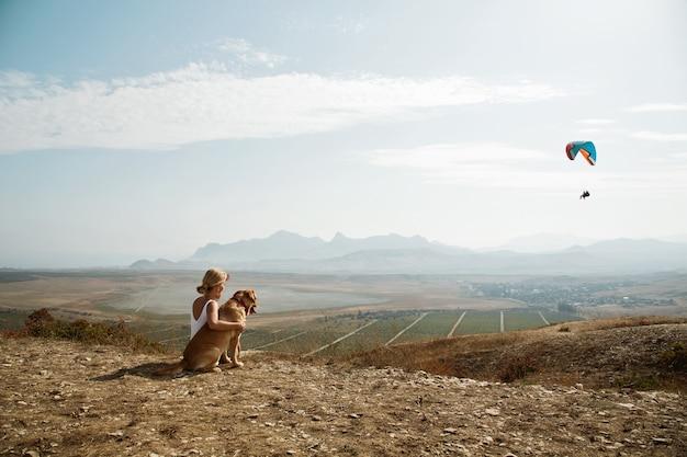Mooi meisje met en hond op de bergtop