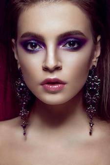 Mooi meisje met fel paarse make-up en sieraden.