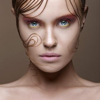 Mooi meisje met felgekleurde make-up en natte haarlokken op het gezicht.