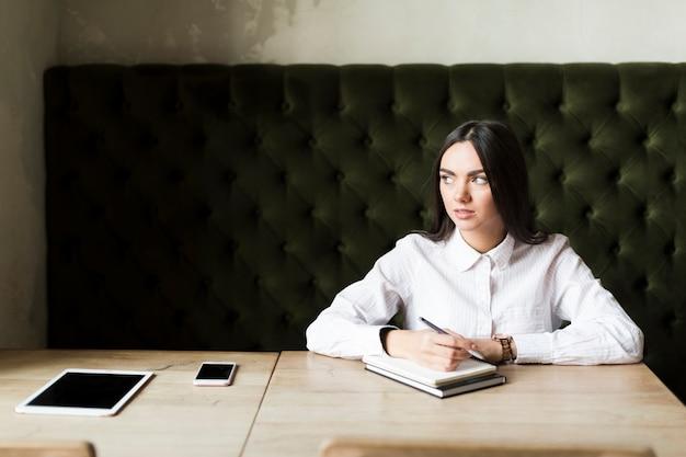 Mooi meisje met gadgets en studies in café