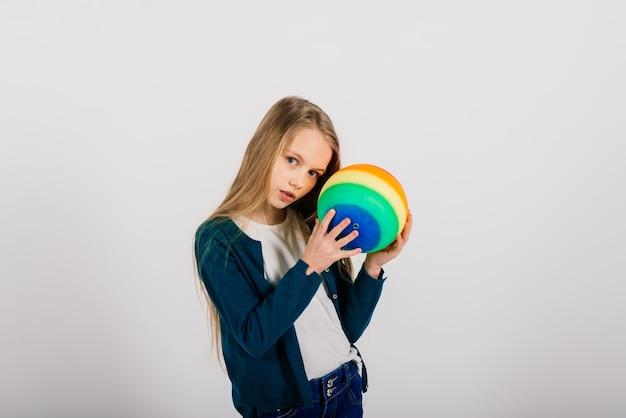 Mooi meisje met gekleurde heldere bal geïsoleerd op wit, studio