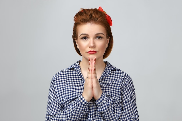 Mooi meisje met gemberhaar en rode lippenstift die palmen samen in gebed drukken. goed uitziende stijlvolle jonge vrouw bidden in studio, camera staren met grote ogen vol hoop en sterk geloof