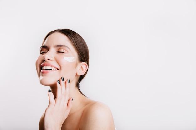Mooi meisje met gesloten ogen lacht op witte muur. model met crème op de huid raakt het gezicht zachtjes aan.