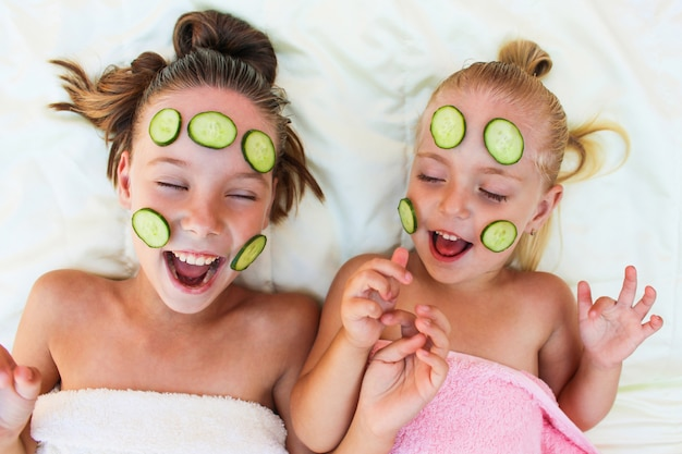 Mooi meisje met gezichtsmasker van komkommer.