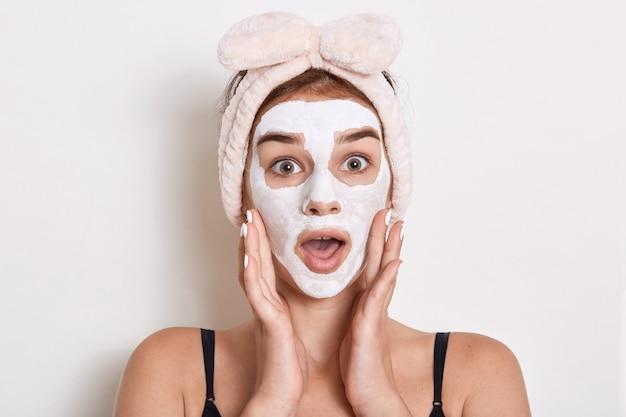 Mooi meisje met gezichtsmasker, verrast vrouw met hoofdband met strik, dame met verbaasde uitdrukking, poseren geïsoleerd op witte achtergrond. huidverzorging en schoonheid.