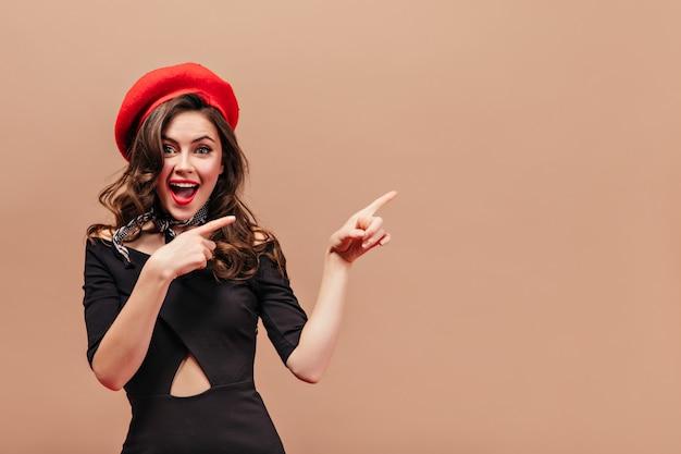 Mooi meisje met golvend haar glimlacht en wijst met haar vingers naar rechts. portret van vrouw in rode hoed en zwarte elegante kleding op beige achtergrond.