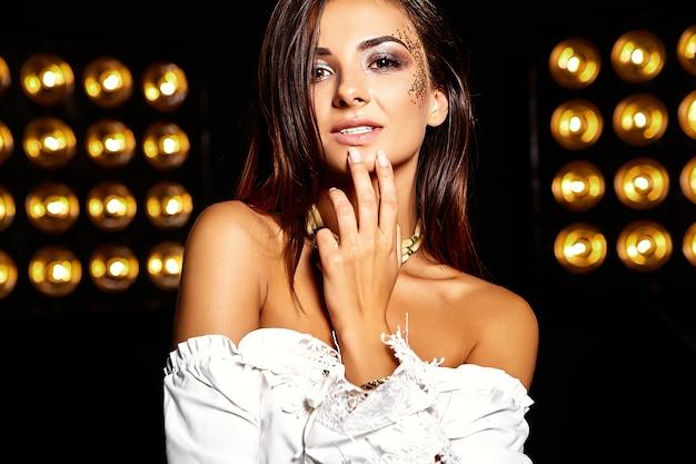 Mooi meisje met gouden glitter op het gezicht. haar lippen aanraken