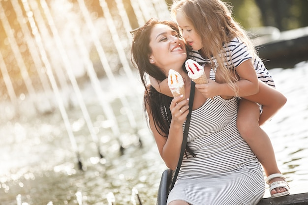 Mooi meisje met haar moeder die roomijs eet